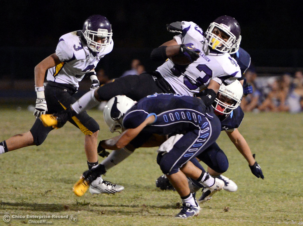 . Pleasant Valley High\'s #3 Brandon Romero (bottom) tackles against Lassen High\'s #43 Case Bennett (top) in the second quarter of their football game at PVHS Asgard Yard Friday, September 6, 2013 in Chico, Calif. (Jason Halley/Chico Enterprise-Record)