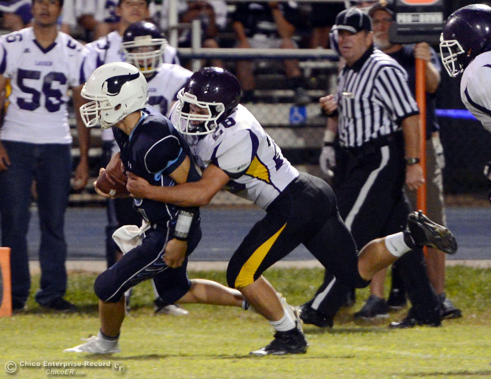 . Pleasant Valley High\'s #12 Trent Darms (left) is tackled against Lassen Highs\' #28 John Cluck (right) in the third quarter of their football game at PVHS Asgard Yard Friday, September 6, 2013 in Chico, Calif. (Jason Halley/Chico Enterprise-Record)