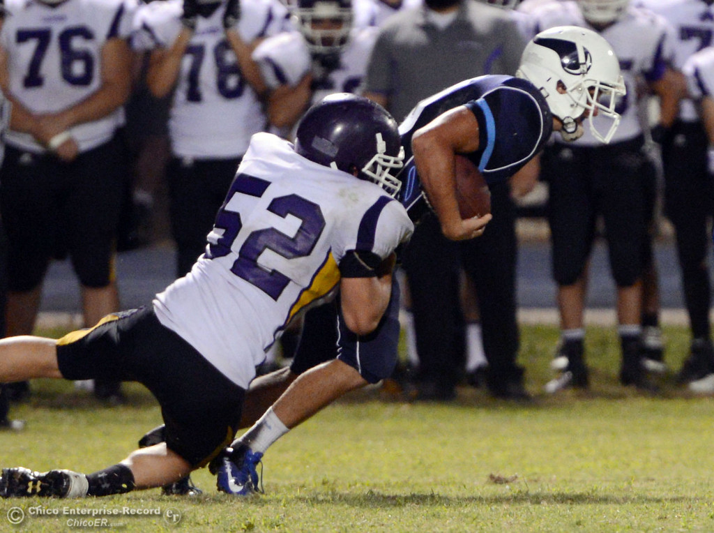 . Pleasant Valley High\'s #10 Tucker LaRue (right) is tackled against Lassen High\'s #52 Tyler Clark (left) in the fourth quarter of their football game at PVHS Asgard Yard Friday, September 6, 2013 in Chico, Calif. (Jason Halley/Chico Enterprise-Record)