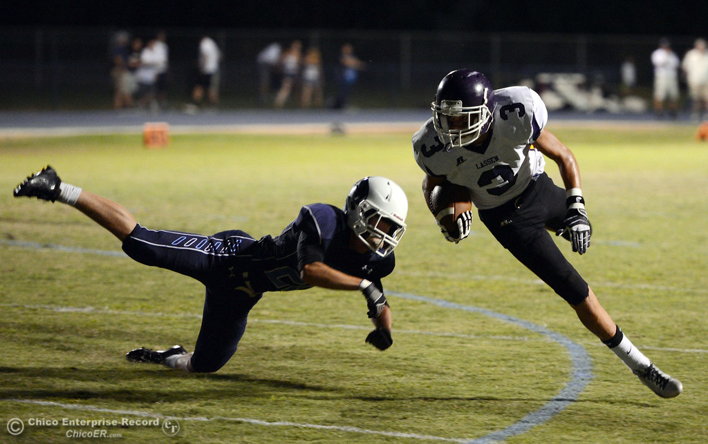 . Pleasant Valley High\'s #22 Jake Dani (left) tackles against Lassen High\'s #3 Quinn Thompson (right) in the first quarter of their football game at PVHS Asgard Yard Friday, September 6, 2013 in Chico, Calif. (Jason Halley/Chico Enterprise-Record)