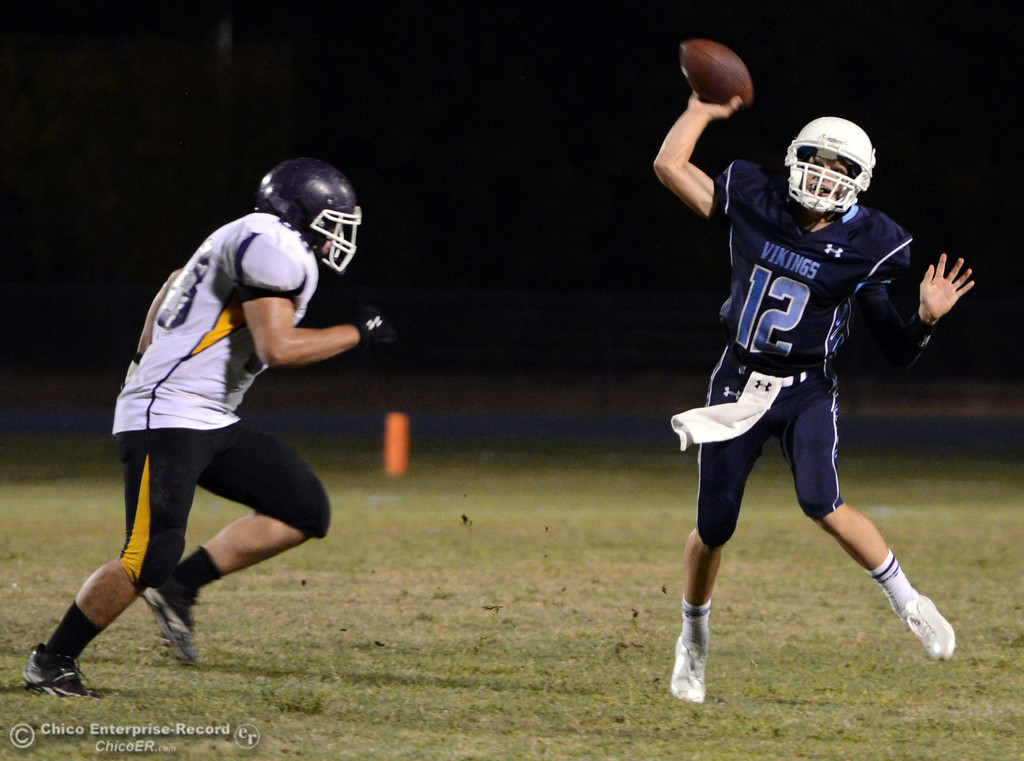 . Pleasant Valley High\'s #12 Trent Darms (right) throws a pass against Lassen High\'s #68 Jacob Gregg (left) in the second quarter of their football game at PVHS Asgard Yard Friday, September 6, 2013 in Chico, Calif. (Jason Halley/Chico Enterprise-Record)