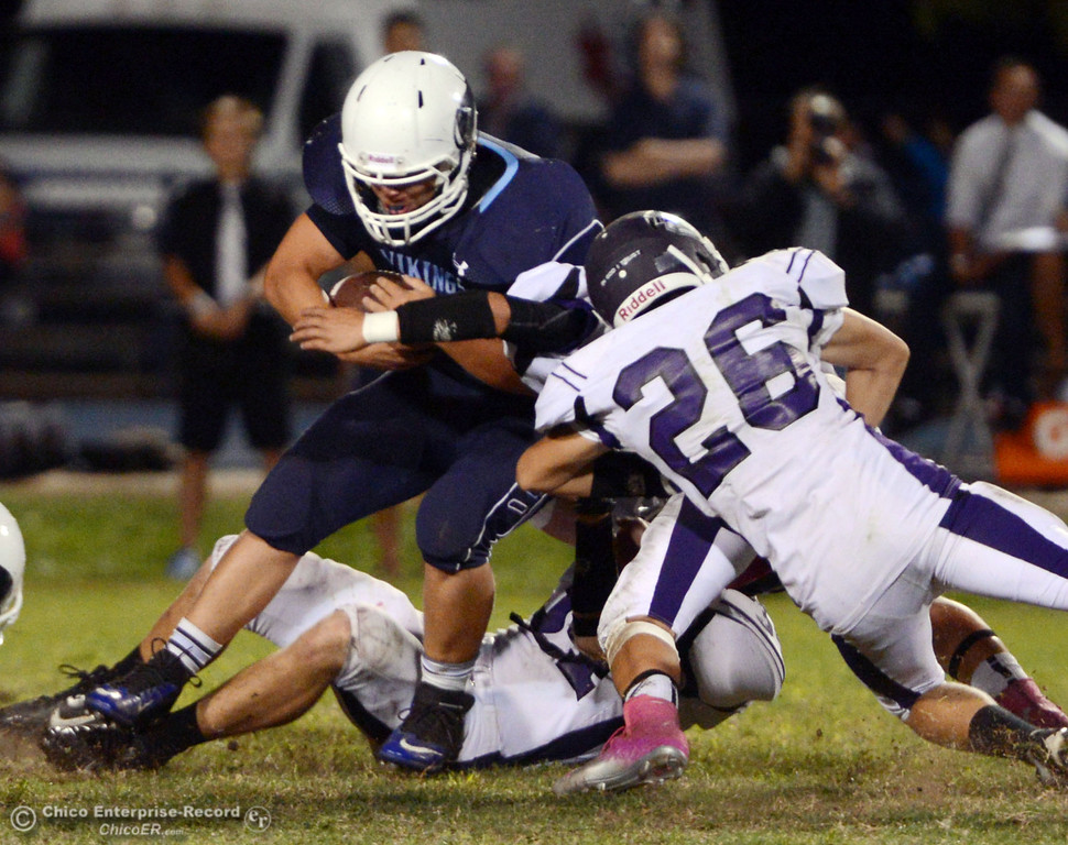 . Pleasant Valley High\'s #9 Houston McGowan (left) is tackled against Oroville High\'s #26 Dylan Shoemaker (right) and #34 Thomas Miller (bottom) in the third quarter of their football game at PVHS Asgard Yard Friday, September 20, 2013, in Chico, Calif. (Jason Halley/Chico Enterprise-Record)