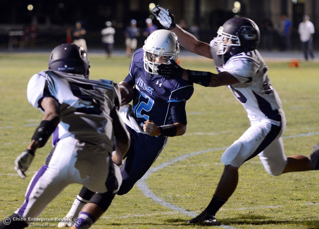 . Pleasant Valley High\'s #12 Trent Darms (left) breaks tackles to rush for a touchdown against Oroville High\'s #5 Kahiel Wyatt (left) and #20 Brandon Tewksbury (right) in the second quarter of their football game at PVHS Asgard Yard Friday, September 20, 2013, in Chico, Calif. (Jason Halley/Chico Enterprise-Record)