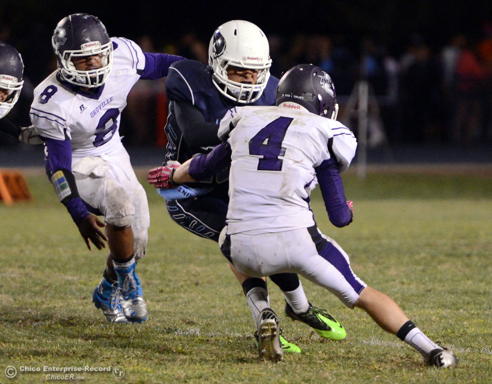 . Pleasant Valley High\'s #20 Bryan Esquivel (center) is tackled against Oroville High\' s#8 James Jones (left) and #4 Antony Ramsey (right) in the fourth quarter of their football game at PVHS Asgard Yard Friday, September 20, 2013, in Chico, Calif. (Jason Halley/Chico Enterprise-Record)