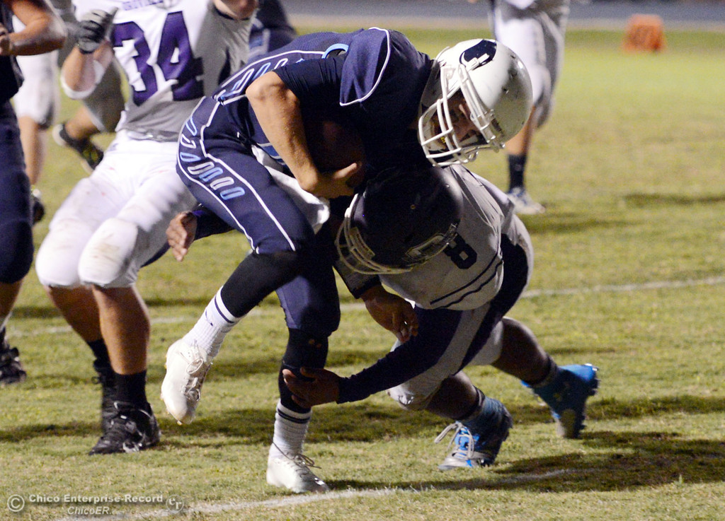. Pleasant Valley High\'s #12 Trent Darms (left) is tackled against Oroville High\' #8 James Jones (right) in the second quarter of their football game at PVHS Asgard Yard Friday, September 20, 2013, in Chico, Calif. (Jason Halley/Chico Enterprise-Record)