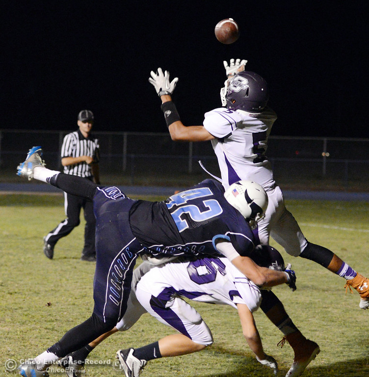 . Pleasant Valley High\'s #42 Chad Olsen (center) has his pass broken up by Oroville High\'s #26 Dylan Shoemaker (bottom) and #5 Kahliel Wyatt (top) in the second quarter of their football game at PVHS Asgard Yard Friday, September 20, 2013, in Chico, Calif. (Jason Halley/Chico Enterprise-Record)