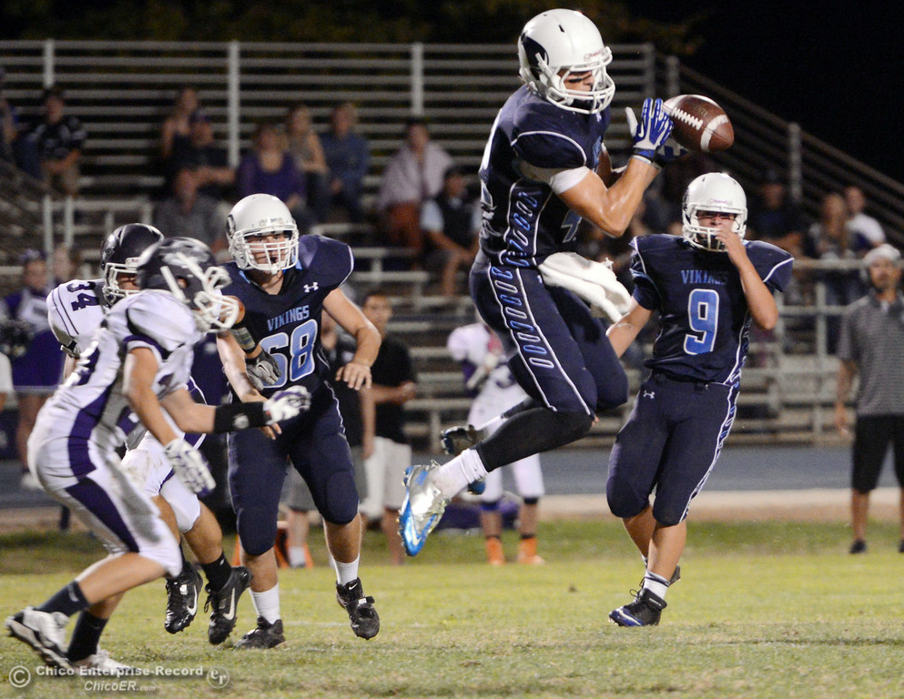. Pleasant Valley High\'s #42 Chad Olsen (center) completes a catch against Oroville High in the first quarter of their football game at PVHS Asgard Yard Friday, September 20, 2013, in Chico, Calif. (Jason Halley/Chico Enterprise-Record)