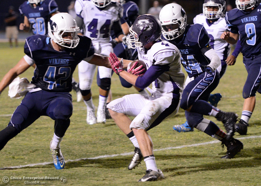 . Oroville High\'s #4 Antony Ramsey (center) is tackled against Pleasant Valley High\'s #42 Chad Olsen (left) and #34 Cale Crawford (right) in the second quarter of their football game at PVHS Asgard Yard Friday, September 20, 2013, in Chico, Calif. (Jason Halley/Chico Enterprise-Record)