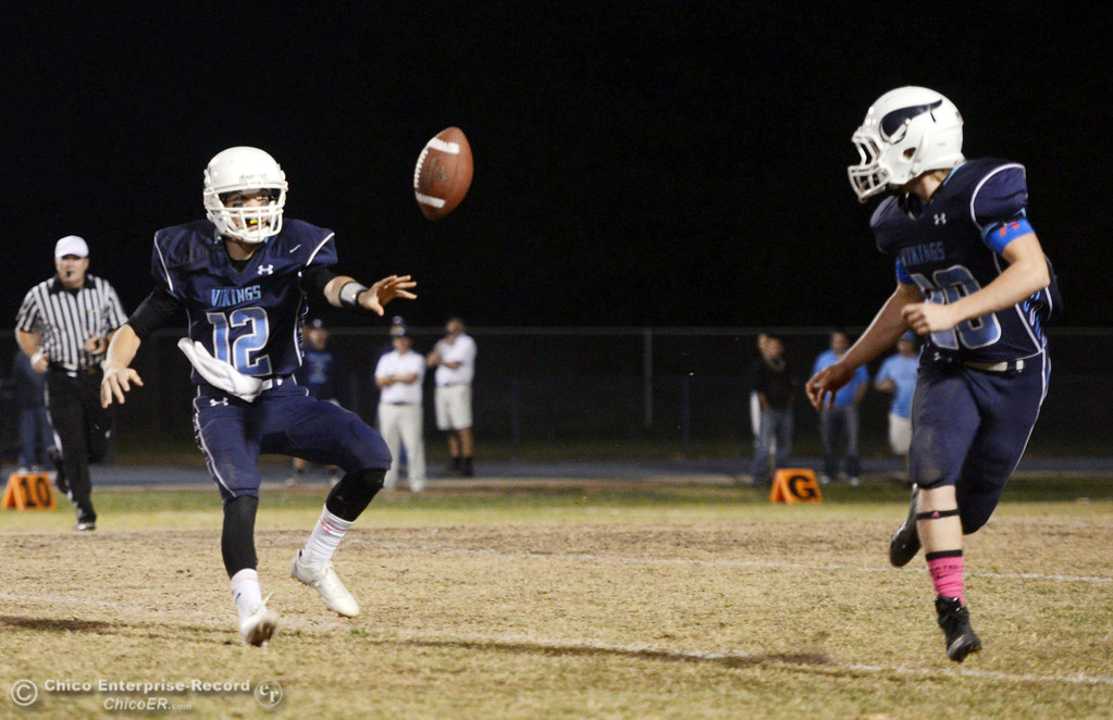 . Pleasant Valley High\'s #12 Trent Darms (left) tosses the ball to #28 Dylan Batie (right) against Shasta High in the second quarter of their football game at PVHS Asgard Yard Friday, October 18, 2013 in Chico, Calif.  (Jason Halley/Chico Enterprise-Record)