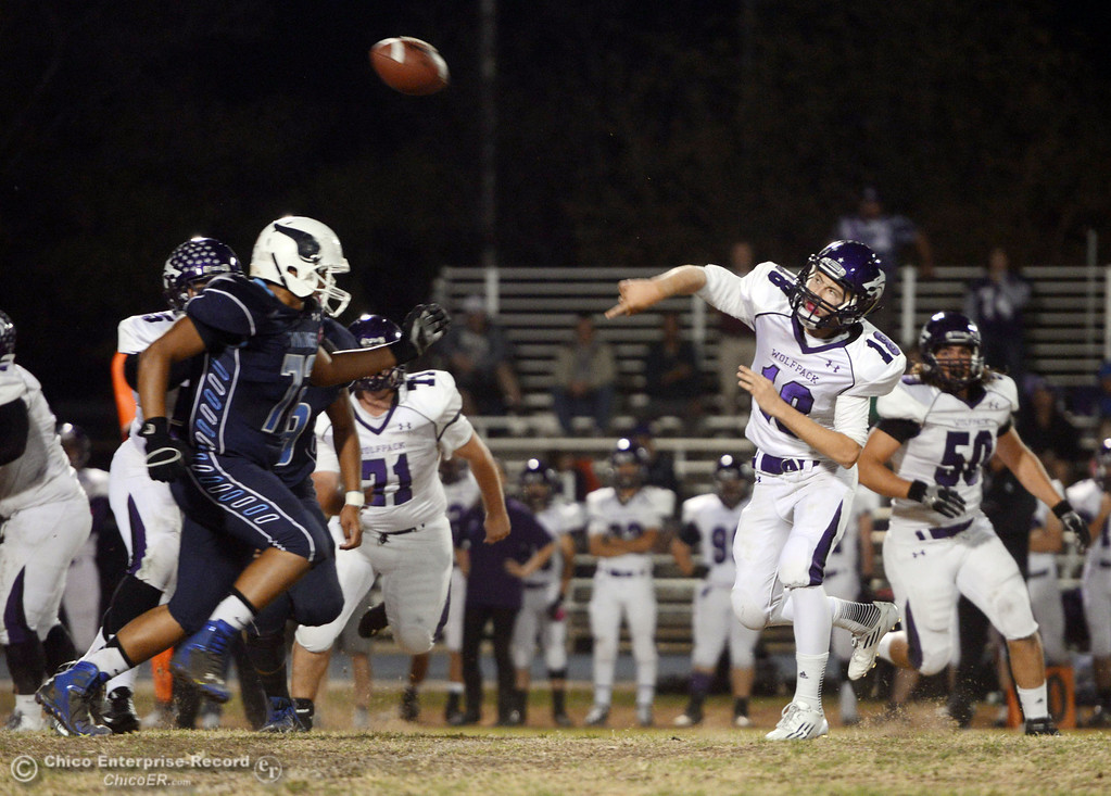 . Pleasant Valley High\'s #72 Christian Darden (left) pressures against Shasta High\'s #18 Bailey Odell (right) in the first quarter of their football game at PVHS Asgard Yard Friday, October 18, 2013 in Chico, Calif.  (Jason Halley/Chico Enterprise-Record)