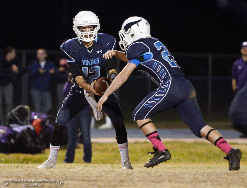 . Pleasant Valley High\'s #12 Trent Darms (left) fakes a hand off to #28 Dylan Batie (right) against Shasta High in the second quarter of their football game at PVHS Asgard Yard Friday, October 18, 2013 in Chico, Calif.  (Jason Halley/Chico Enterprise-Record)