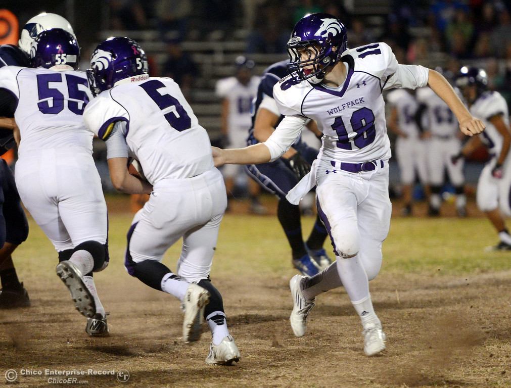 . Shasta High\'s #18 Bailey Odell (right) hands off to #5 Jake Callaway (left) against Pleasant Valley High in the first quarter of their football game at PVHS Asgard Yard Friday, October 18, 2013 in Chico, Calif.  (Jason Halley/Chico Enterprise-Record)