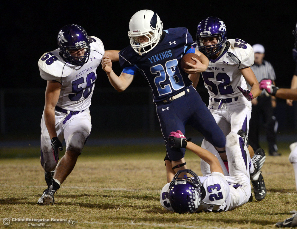 . Pleasant Valley High\'s #28 Dylan Batie (center) rushes against Shasta High\'s #23 Ryan Pallato (bottom) #56 Nic Ariagno (left) and #52 Jake Thengvall (right) in the second quarter of their football game at PVHS Asgard Yard Friday, October 18, 2013 in Chico, Calif.  (Jason Halley/Chico Enterprise-Record)