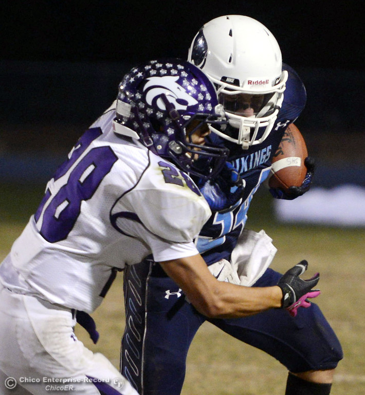 . Pleasant Valley High\'s #34 Cale Crawford (right) is tackled against Shasta High\'s #28 Anthony Archuleta (left) in the second quarter of their football game at PVHS Asgard Yard Friday, October 18, 2013 in Chico, Calif.  (Jason Halley/Chico Enterprise-Record)