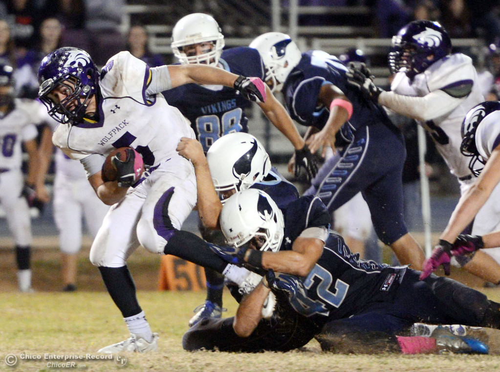 . Pleasant Valley High\'s #42 Chad Olsen (bottom) tackles against Shasta High\'s #5 Jake Callaway (left) in the fourth quarter of their football game at PVHS Asgard Yard Friday, October 18, 2013 in Chico, Calif.  (Jason Halley/Chico Enterprise-Record)