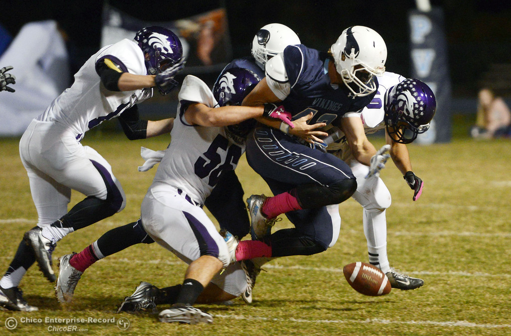 . Pleasant Valley High\'s #42 Chad Olsen (center) fumbles the ball  against Shasta High in the first quarter of their football game at PVHS Asgard Yard Friday, October 18, 2013 in Chico, Calif.  (Jason Halley/Chico Enterprise-Record)