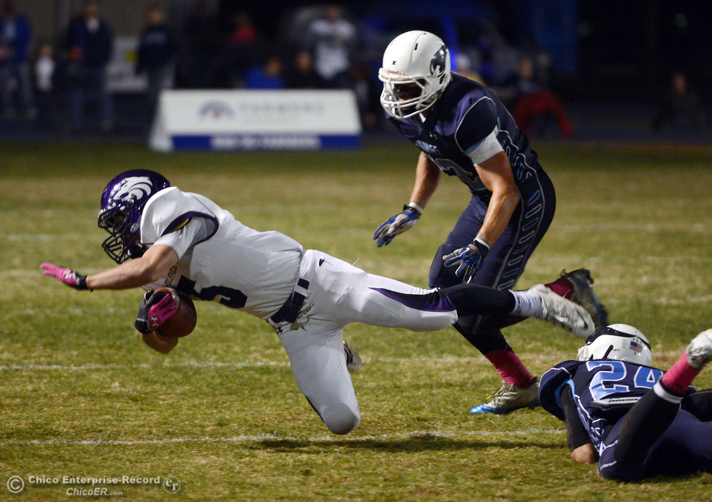 . Shasta High\'s #5 Jake Callaway (left) is tackled by Pleasant Valley High\'s #24 Jack Soza (bottom) with #42 Chad Olsen (right) looking on  in the first quarter of their football game at PVHS Asgard Yard Friday, October 18, 2013 in Chico, Calif.  (Jason Halley/Chico Enterprise-Record)