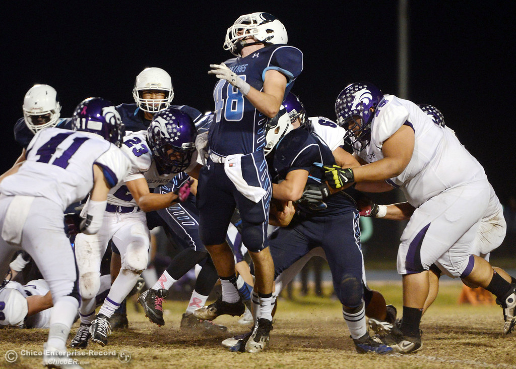 . Pleasant Valley High\'s #48 Logan O\'Sullivan (center) is hit in the back by #28 Dylan Batie on a carry against Shasta High in the second quarter of their football game at PVHS Asgard Yard Friday, October 18, 2013 in Chico, Calif.  (Jason Halley/Chico Enterprise-Record)