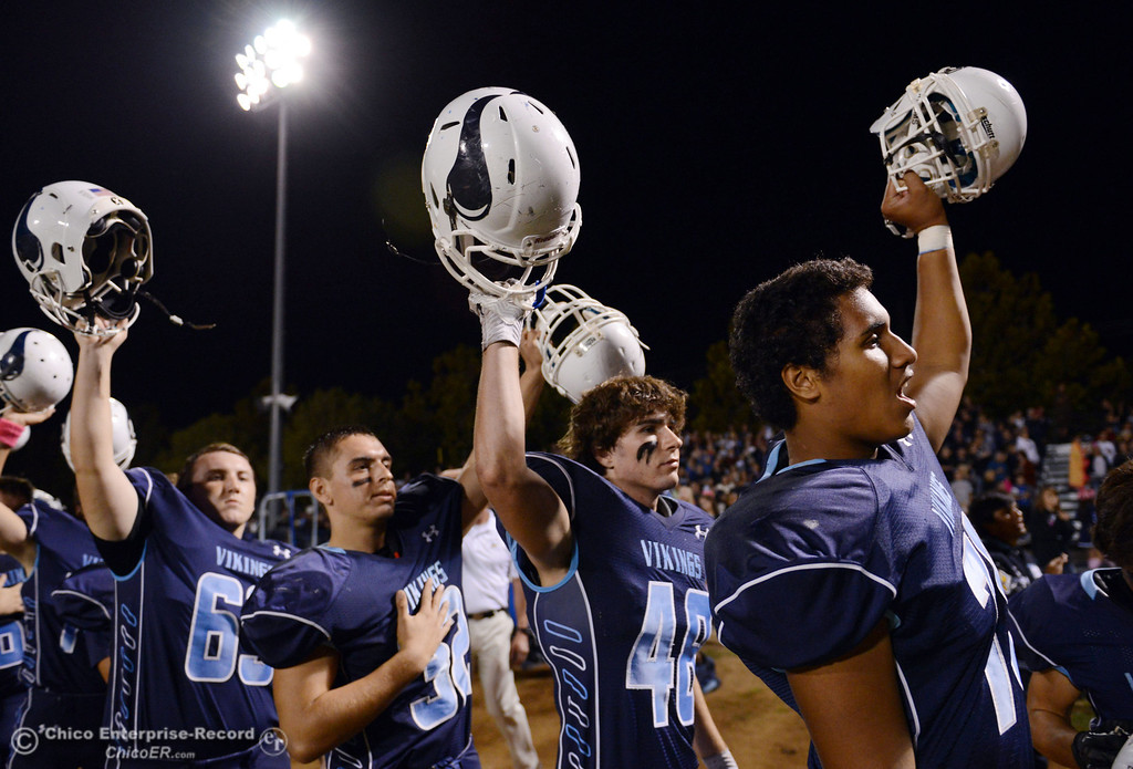 . Pleasant Valley High\'s #63 Harrison Carter, #32 Jon Acevedo, #28 Logan O\'Sullivan, and #78 Alex Marquez (left to right) raise their helmets against Shasta High before the first quarter of their football game at PVHS Asgard Yard Friday, October 18, 2013 in Chico, Calif.  (Jason Halley/Chico Enterprise-Record)