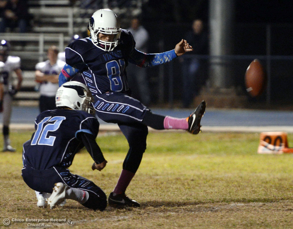 . Pleasant Valley High\'s #81Brian Lerch (right) kicks the extra point from #12 Trent Darms (left) against Shasta High in the first quarter of their football game at PVHS Asgard Yard Friday, October 18, 2013 in Chico, Calif.  (Jason Halley/Chico Enterprise-Record)