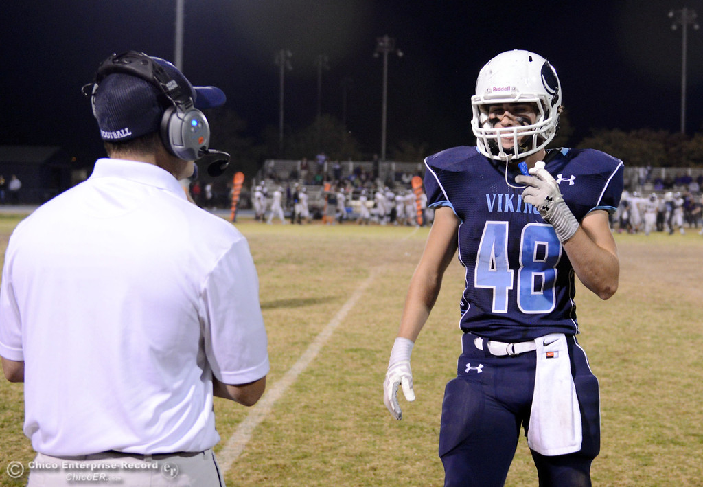 . Pleasant Valley High coach Mark Cooley (left) talks with #48 Logan O\'Sullivan (right) against Shasta High in the first quarter of their football game at PVHS Asgard Yard Friday, October 18, 2013 in Chico, Calif.  (Jason Halley/Chico Enterprise-Record)