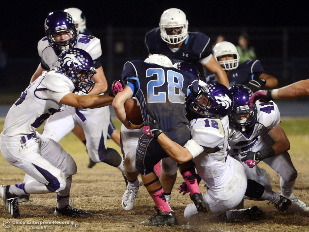 . Pleasant Valley Highs\' #28 Dylan Batie (center) is tackled against Shasta High\'s #12Colton Murrison (right) in the second quarter of their football game at PVHS Asgard Yard Friday, October 18, 2013 in Chico, Calif.  (Jason Halley/Chico Enterprise-Record)