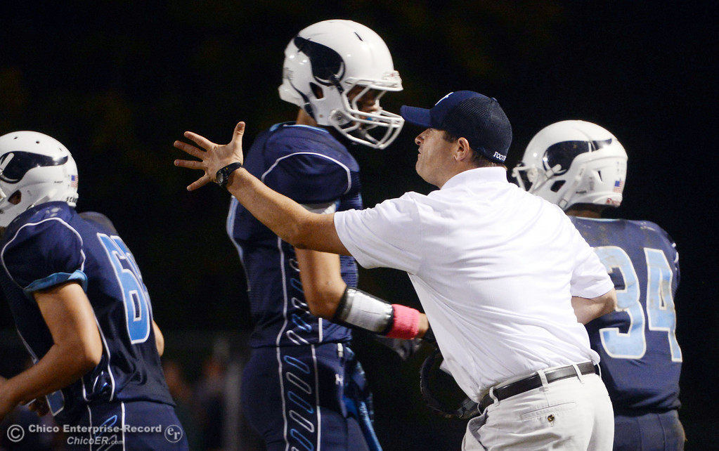. Pleasant Valley High\'s coach Mark Cooley makes the calls against Shasta High in the second quarter of their football game at PVHS Asgard Yard Friday, October 18, 2013 in Chico, Calif.  (Jason Halley/Chico Enterprise-Record)