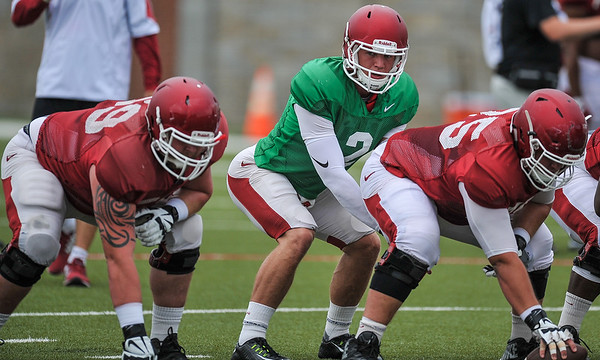 Rafe Peavey prepares to take the snap from Zach Rogers (75) with Marcus Danenhauer (59) at his side at the Razorback football practice on Tuesday, August 18, 2015 at the Fred W. Smith Football Center in Fayetteville, Arkansas.   (Alan Jamison, Nate Allen Sports Service).