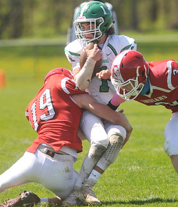 Pembroke quarterback Connor Peterson gets brought down by Red Jacket's Andrew Damore (19) and Kyle Damore. Photo by Jack Haley for Daily Messenger.