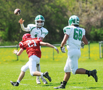 Pembroke starting quarterback Connor Peterson gets the pass off for before taking a hit from Red Jacket's Parker Moore Photo by Jack Haley for Daily Messenger.
