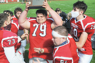 Red Jacket senior captain Blaze Hickson holds up the sectional trophy after he and teammates posted an 82-6 win over Pembroke. Photo by Jack Haley for Daily Messenger.