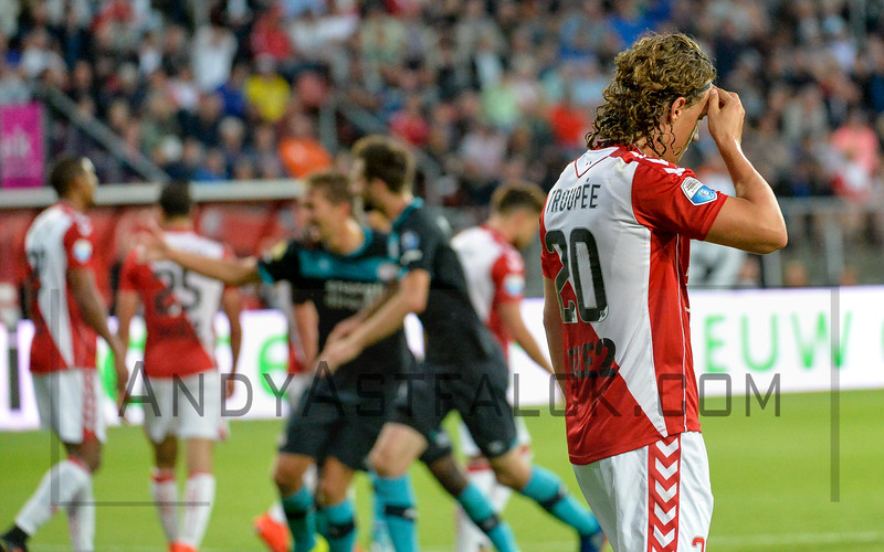 PSV celebrate while Giovanni Troupee from Utrecht holds his head in despair, during the Dutch Eredivisie Football match between FC Utrecht and PSV Eindhoven at Stadion Galgenwaard in Utrecht on August 6, 2016.