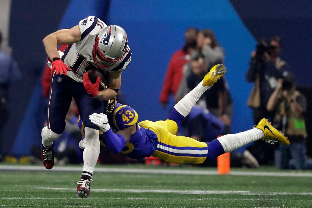 . New England Patriots\' Julian Edelman (11) breaks a tackle by Los Angeles Rams\' John Johnson III (43), during the second half of the NFL Super Bowl 53 football game Sunday, Feb. 3, 2019, in Atlanta. (AP Photo/Jeff Roberson)