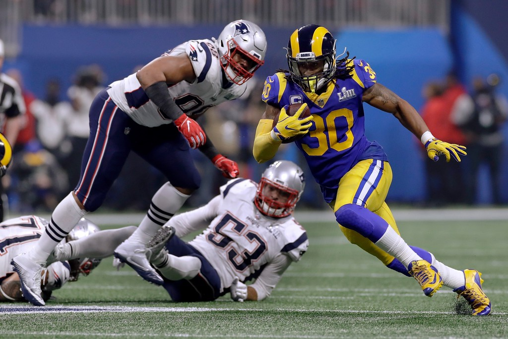. Los Angeles Rams\' Todd Gurley II (30) runs from New England Patriots\' Trey Flowers, left, and Kyle Van Noy (53) during the second half of the NFL Super Bowl 53 football game Sunday, Feb. 3, 2019, in Atlanta. The play was nullified by a Rams holding penalty. (AP Photo/Carolyn Kaster)