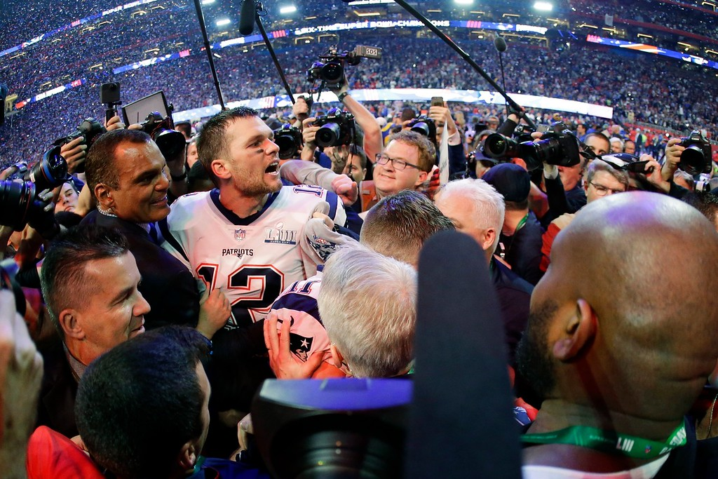 . New England Patriots\' Tom Brady (12) is surrounded by media on the field, after the NFL Super Bowl 53 football game against the Los Angeles Rams, Sunday, Feb. 3, 2019, in Atlanta. The Patriots won 13-3. (AP Photo/Mark Humphrey)