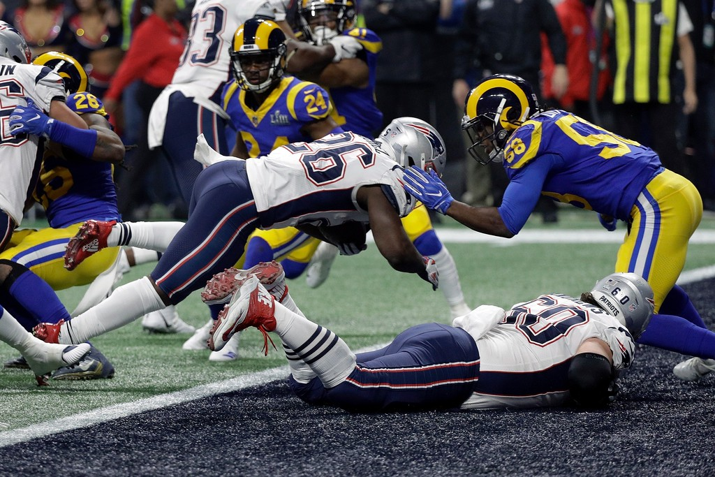 . New England Patriots\' Sony Michel (26) dives over the goal line for a touchdown in front of Los Angeles Rams\' Cory Littleton (58) during the second half of the NFL Super Bowl 53 football game Sunday, Feb. 3, 2019, in Atlanta. (AP Photo/David J. Phillip)