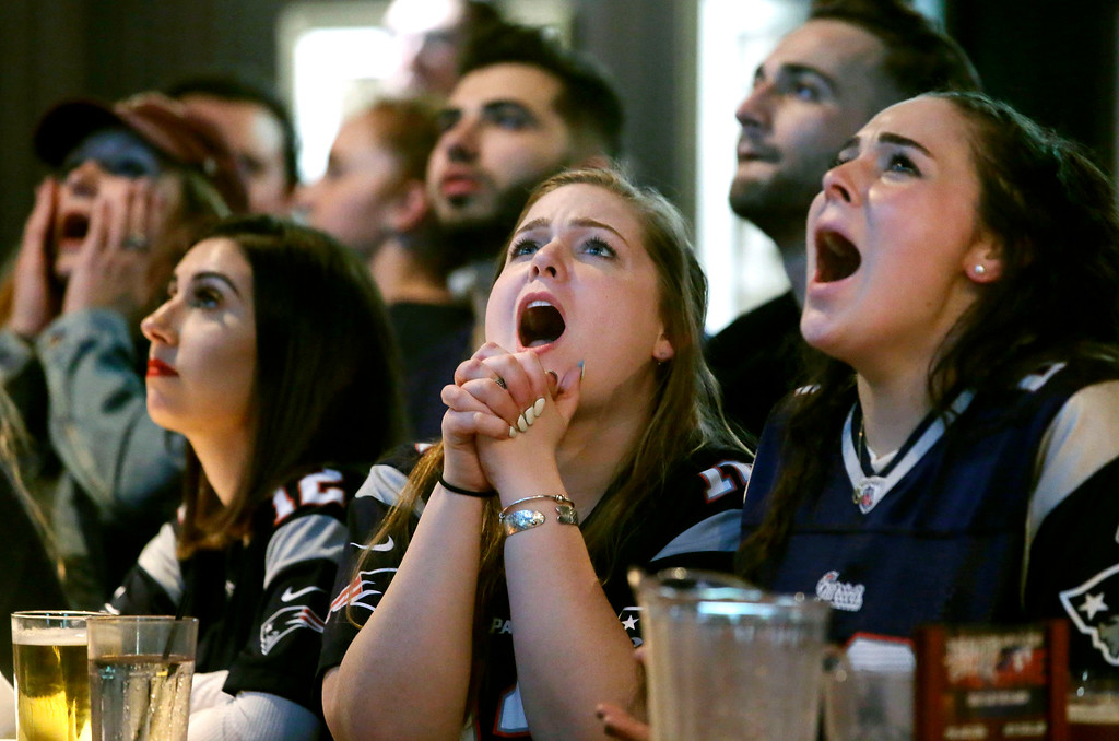 . Kathleen Doherty, center, of Woburn, Mass., reacts with other fans at a Boston bar while watching the New England Patriots\' final drive during the first half of the NFL Super Bowl 52 football game between the Patriots and the Philadelphia Eagles in Minneapolis, Sunday, Feb. 4, 2018. (AP Photo/Steven Senne)