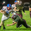 Comets quarterback Brandon Kinser (9) tries hard to avoid the grasp of Ethan Rogers in the first half. Winamac went on to defeat Caston by a score of 47-8. Fran Ruchalski | Pharos-Tribune