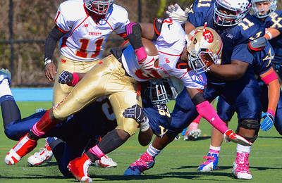 101312, Westwood, MA - Everett's Jalen Felix gets brought down by Xaverian's Maurice Hurst Jr., right, as Elijah Jolly wraps his legs. Herald photo by Ryan Hutton.
