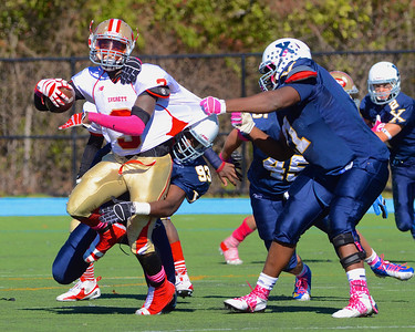 101312, Westwood, MA - Everett's Jalen Felix gets grabbed by Xaverian's Maurice Hurst Jr., right, as Elijah Jolly wraps his legs. Herald photo by Ryan Hutton.