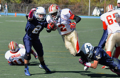 101312, Westwood, MA - Everett's Jakarrie Washington, center, tries to carry the ball past Xaverian's AJ King, left, and Joe DeNucci Jr., right. Herald photo by Ryan Hutton.
