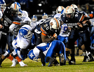 Running back Calvin Middleton (20) protects the ball as he gets the hit from the Peachtree Ridge defense Friday night.