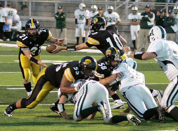 Record-Eagle/Keith King<br /> Traverse City Central's Mack Sovereign hands the ball off to Ben Broad as teammates Vaimagalo Taula, bottom left, and Brad Keller, bottom right, provide blocks prior to Broad scoring a touchdown against Alpena Friday, September 10, 2010 at Thirlby Field.