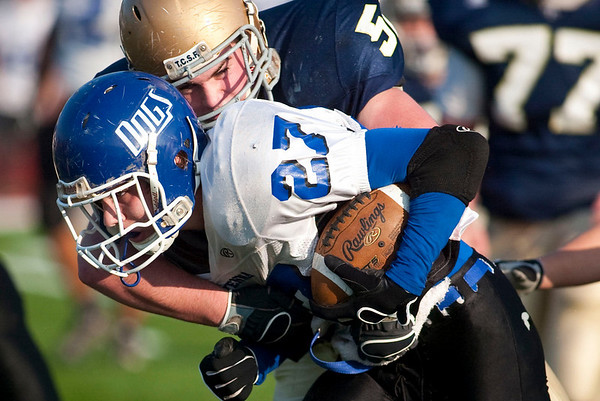 Record-Eagle/Jan-Michael Stump<br /> Traverse City St. Francis defensive lineman Kyle Gallagher (52) tackles  Ravenna running back Josh VanderWagen (27) in the third quarter of Saturday's state semifinal game.