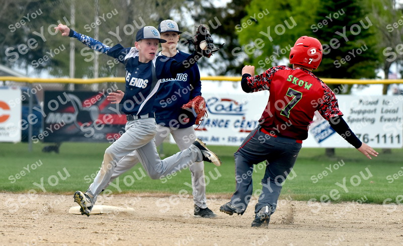 -Messenger photo by Britt Kudla<br /> Gavin Bacon of Fort Dodge Legends 12U attempts to tag Ankeny Outlaws Ethan Skow during Taco Tico Throwdown on Saturday at Rogers Park