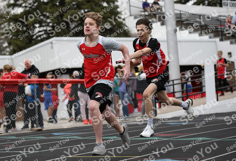 -Messenger photo by Britt Kudla<br /> Fort Dodge 8th grader Talen warland (right) handoff the baton to Kade Bedlhe during 4x200 relays on Monday inside Dodgers Stadium