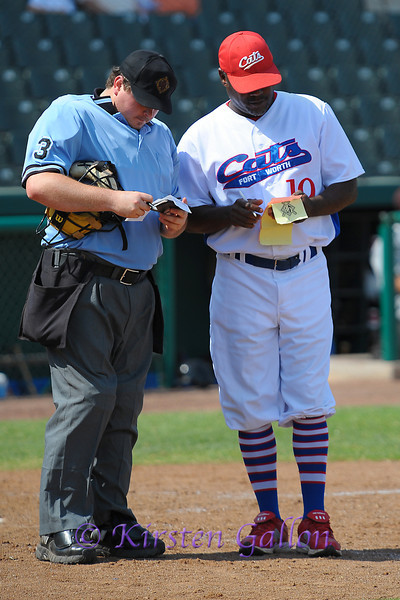 Manager Curtis Wilkerson makes some line-up changes with the home plate umpire.