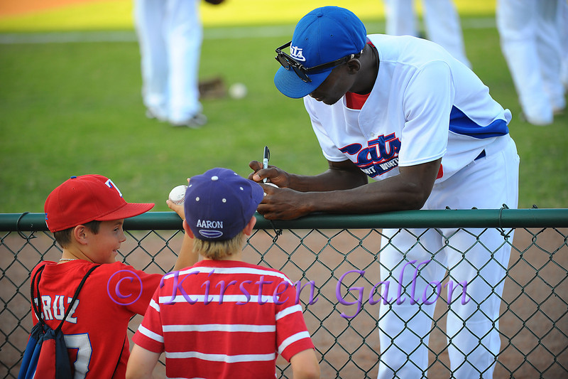 Outfielder Randall Thorpe makes some young fans happy by signing their baseball.