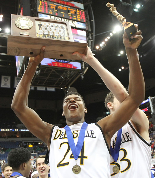 DeLaSalle senior forward Joshua Collins holds the state championship trophy and his trophy for being named to the Class AAA All Tournament Team. Dave Hrbacek/The Catholic Spirit
