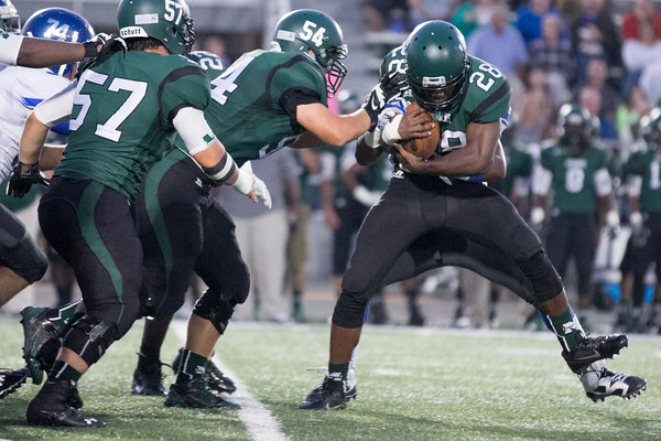 Muskogee Roughers hosting the Sapulpa Chieftains.  September 26, 2014 - Muskogee, OK.   Jacouri Freeman holding the ball tight as he's brought down by Chieftain #74